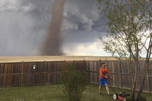 Taglia l'erba con il tornado alle spalle: la foto diventa virale