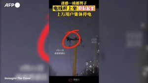 Cina: uomo si arrampica  su palo della luce per fare le flessioni. Blackout in tutta la città